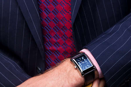 Close up image of a businessman checking the time on his wrist watch.