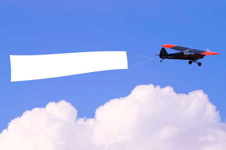 Photo pour An airplane flying through the sky pulling a blank white banner to add your own message. - image libre de droit
