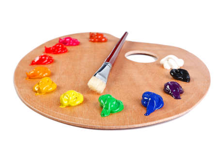 a wooden artists palette loaded with various colour paints and brush