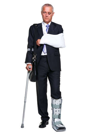 Photo pour Badly injured businessman walking on cructhes carrying a briefcase, isolated on a white background. - image libre de droit
