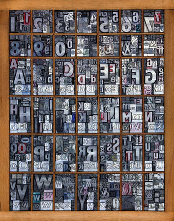 Photo of a printing tray full of old used metal letterpress in mixed fonts, all the letters of the alphabet and numbers from 0-9 mixed in with some punctuation marks and symbols.