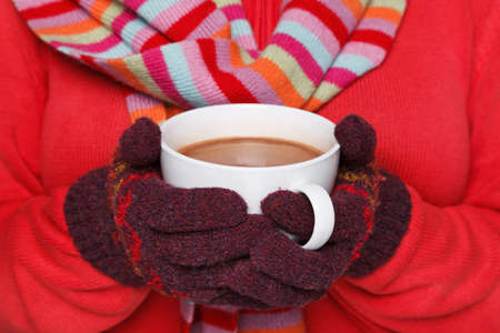 Photo pour Close up midriff photo of a woman wearing a red jumper, woolen gloves and a scarf holding a mug full of hot chocolate, good image to convey a feeling of winter and warmth. - image libre de droit