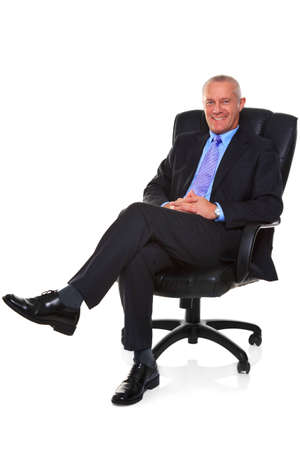 Photo of a mature businessman wearing a smart suit and tie, sat in a leather executive chair with his legs crossed and smiling to camera, isolated on a white background with natural chair relection.