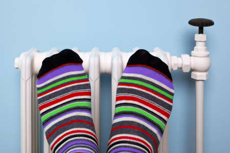 Photo of a persons feet in striped socks warming them against an old traditional cast iron radiator.