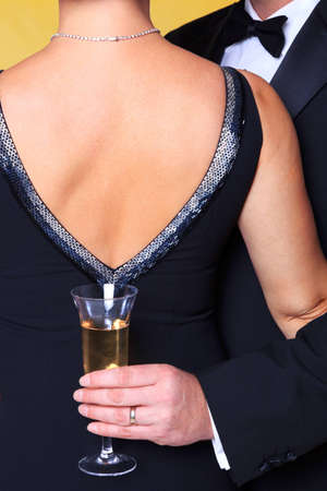 Photo of a couple in black tie evening wear, rear view of the womans back with the man holding a glass of champagne.