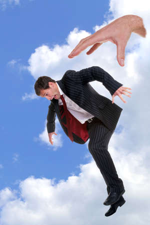 Concept photo of a businessman being dropped out of the sky by the hand of God, could be used to portray themes such as fear, fright, nightmare, refusal, dismissal, rejection, failure or disapproval. Plus any other you can think of.