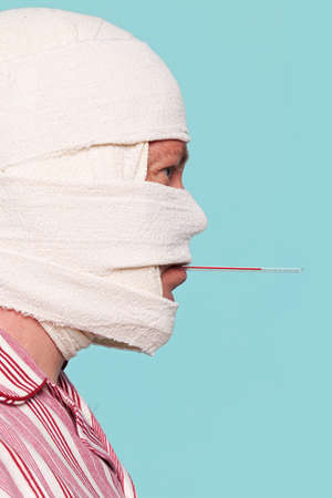 Photo of a Hospital patient with a bandaged head and a thermometer in his mouth having his temperature taken.