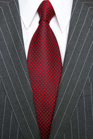 Photo of a grey pinstripe suit with plain white shirt and red patterned tie
