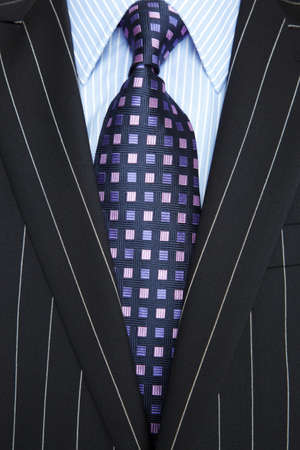 Photo of a black pinstripe suit with blue striped shirt and purple and blue patterned tie