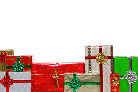 A group of gift wrapped Christmas presents with bows and ribbons, isolated on a white background and positioned lower frame for you to add a message above.