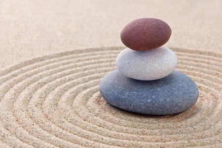 Three pebbles stacked on a circular raked zen garden