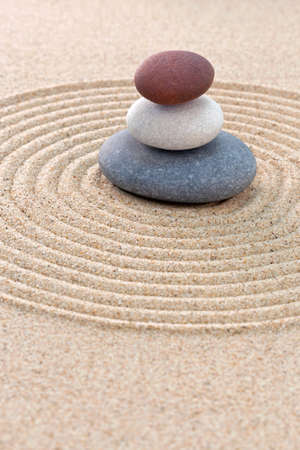 Three pebbles stacked on a circular raked zen garden