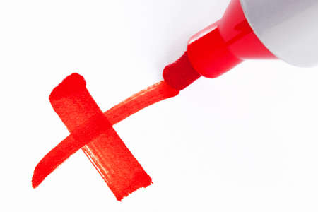 Close-up photo of a big red felt tip marker pen writing a cross X on white paper