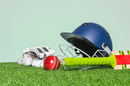 Photo for Cricket equipment with bat, ball, helmet and gloves on grass with green background. - Royalty Free Image