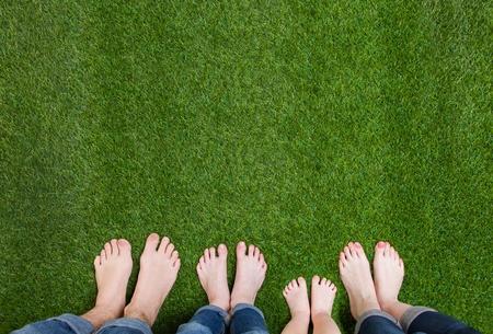 Photo pour Family legs standing on green grass - image libre de droit
