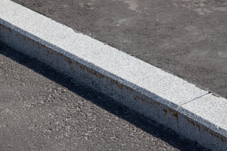 white curb stone border and asphalt road