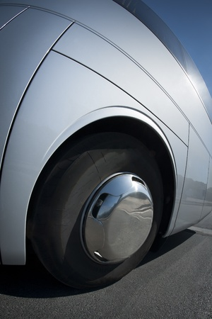 Big wheel and tire close up on a white bus