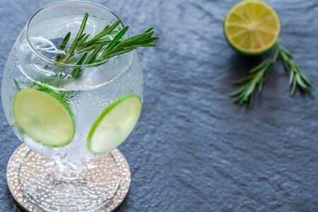 Photo for Gin and tonic cocktail with lime and rosemary - refreshing summer alkoholic drink - Royalty Free Image