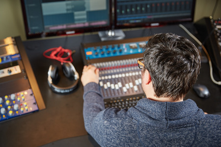 Sound engineer is working on a mixing console in a sound studio