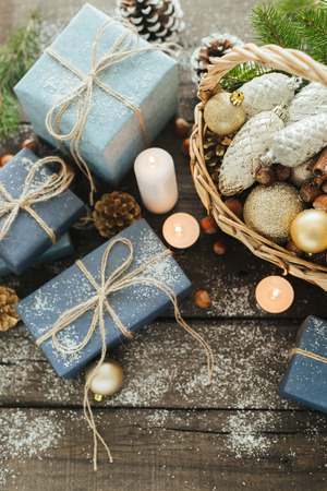 Photo for Festive Gifts with Boxes, Candle, Snow, Coniferous, Basket, Cinnamon, Pine Cones, Nuts on Wooden Background. With space for your text - Royalty Free Image