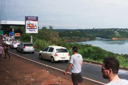 Ciudad Del Este, Paraguay - November 24, 2019: People and Cars Crossing The Friendship Bridge (Spanish: Puente de la Amistad, Portuguese: Ponte da Amizade) is an arch bridge connecting the Brazilian city of Foz do Iguaçu and the Paraguayan city of Ciudad
