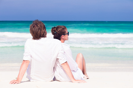 happy young couple in white clothes in sunglasses sitting on beach