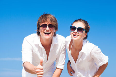 portrait of happy young couple in sunglasses in white clothes smiling outdoors