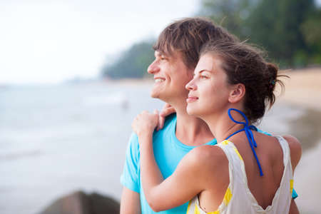 Portrait of happy young couple enjoying their time on tropical beach in the evening