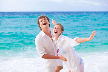 portrait of happy young couple in sunglasses in white clothes enjoying their vacation on tropical beach