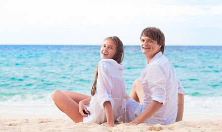 front view of happy young couple in white clothes in sunglasses sitting on beach