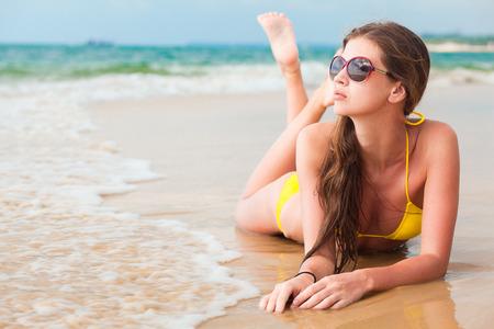 glamorous long haired young woman in bikini and sunglasses on tropical beach