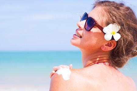 Photo pour Back view of Young woman in sunglasses putting sun cream on shoulder - image libre de droit