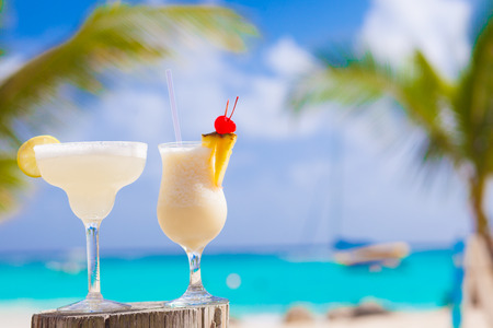 Photo for two perfect cocktails pina colada and margarita with cherry on top, beach background - Royalty Free Image