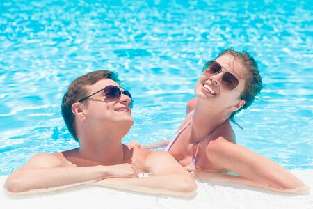 Photo pour young couple relaxing and having fun by the luxury pool - image libre de droit