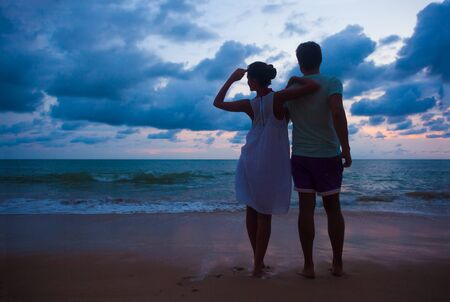 Photo for sunset silhouette of young couple in love hugging at beach - Royalty Free Image