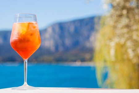 Foto de Glass of delicious Aperol Spritz cocktail on blurred mountains background - Imagen libre de derechos