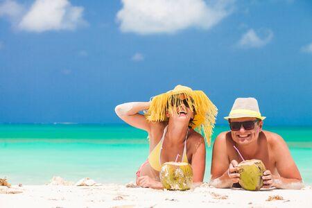 Foto de happy young couple lying on a tropical beach in Barbados and drinking a coconut cocktail - Imagen libre de derechos