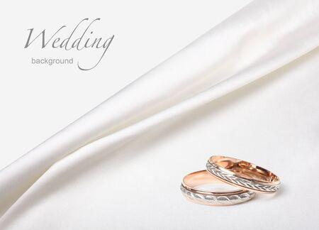 wedding rings on white silk background