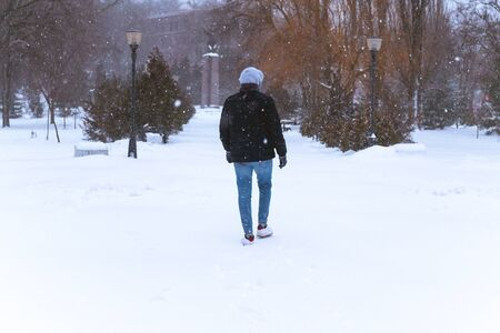 Photo for man walks alone in the winter in the park. lonely man goes among the snow and trees - Royalty Free Image