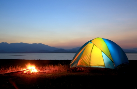 Foto de tent and campfire at sunset,beside the lake - Imagen libre de derechos