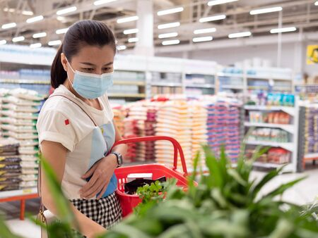Photo for Woman wearing protective mask while grocery shopping in supermarket, Coronavirus contagion fears concept - Royalty Free Image