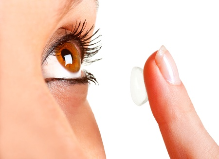 Closeup of a woman inserting a contact lens in her eye