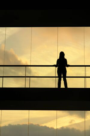 woman in the modern buildind at sunset