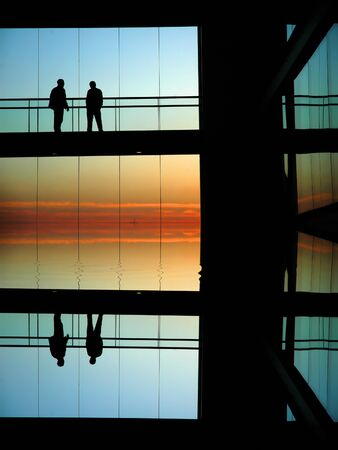 people silhouettes in a modern builing at sunset