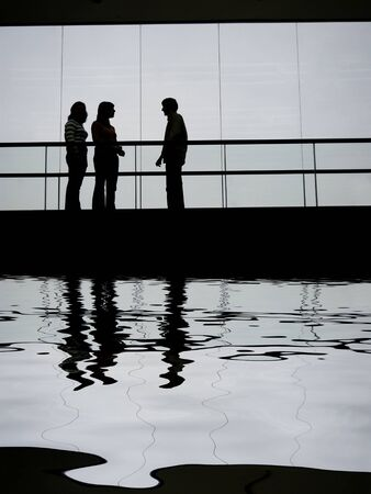 group talking in the building, with water reflection
