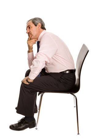 worried mature businessman on a chair, isolated on white