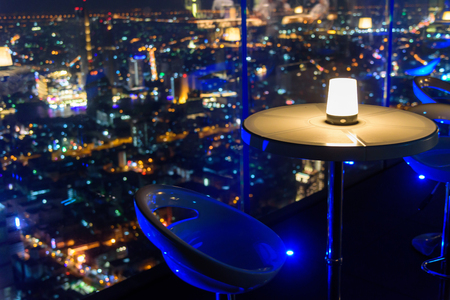 Photo pour empty chair with lighting at rooftop bar on high building - image libre de droit