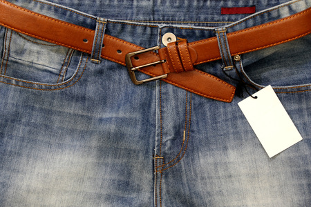 Jeans with a price tag with a leather belt.: Royalty free