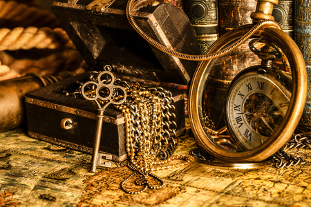 Foto de Antique clock on the background of a magnifying glass, treasure chest with gold and books. Vintage style. 1565 old map of the year. - Imagen libre de derechos