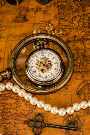 Antique clock in the background of a magnifying glass and books. Vintage style. 1565 old map of the year.